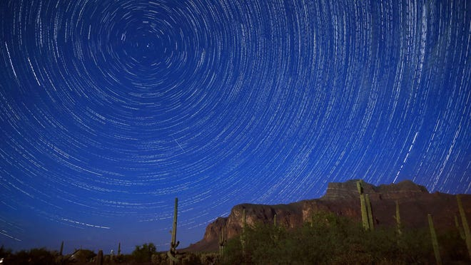 Star trails and a meteor from the Perseid Meteor Shower can be seen beyond the Superstition Mountains early Sunday, Aug. 14, 2016 in Apache Junction.