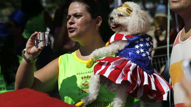 A Carnival reveler carries her dog, dressed as Wonder Woman, during a pet parade in Rio de Janeiro, Brazil. More than 100 pet owners and costumed pets joined the parade on Saturday.