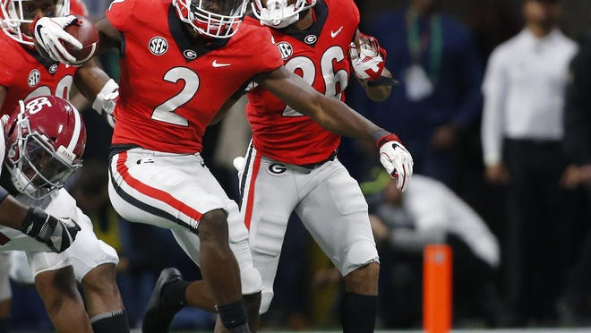 Georgia defensive back Richard LeCounte III (2) moves the ball down the field after making an interception off a pass from Alabama quarterback Tua Tagovailoa (13) in the first half of the Southeastern Conference Championship game between Georgia and Alabama in Atlanta, Saturday, Dec. 1, 2018.
