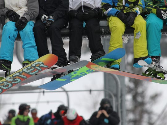 Snowboarders and a skier ride a lift at Granite Peak Ski Area in Rib Mountain.