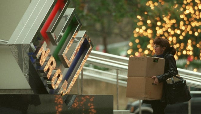 A woman carries a pair of boxes as she leaves the Enron headquarters in Houston on Nov. 28, 2001.