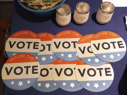 FILE - In this July 14, 2018, file photo, computer mouse pads with Secure the Vote logo on them are seen on a vendor's table at a convention of state secretaries of state in Philadelphia.