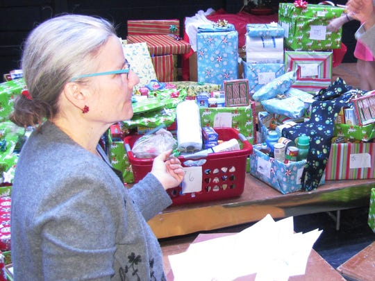 Notre Dame High School campus minister Nancy Roy, left, directs volunteers who delivered gift boxes to 25 needy families in the area following Friday afternoon's Golden Mass.