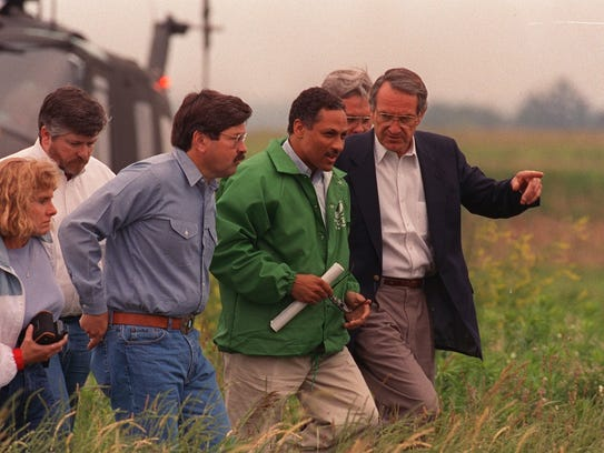 In this 1993 file photo, then-U.S. Agriculture Secretary Mike Espy, flanked by then-Iowa Gov. Terry Branstad and then-U.S.Sen. Tom Harkin, R-Iowa, tour the flood-damaged farm of Dalen Miller in north-central Iowa near Dumont on June 30, 1993.