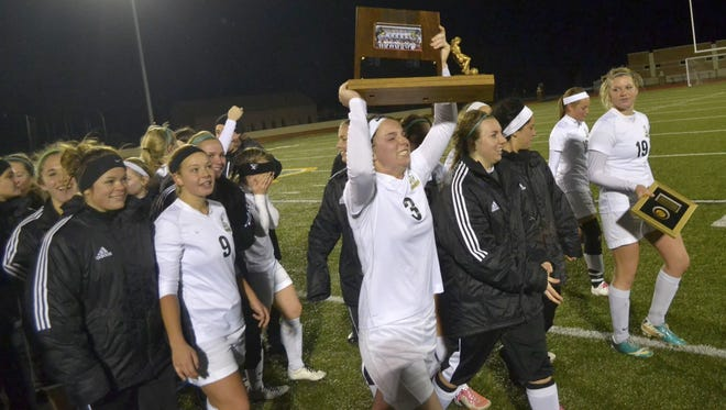 St. Norbert forward Katie Vanden Avond (3) hoists the Midwest Conference championship trophy 2013 Saturday after the Green Knights defeated Monmouth 2-0 to earn their first NCAA tournament berth. Vanden Avond missed the 2014 season with an injury and is returning this year 34 goals shy of breaking the NCAA Division III career record.