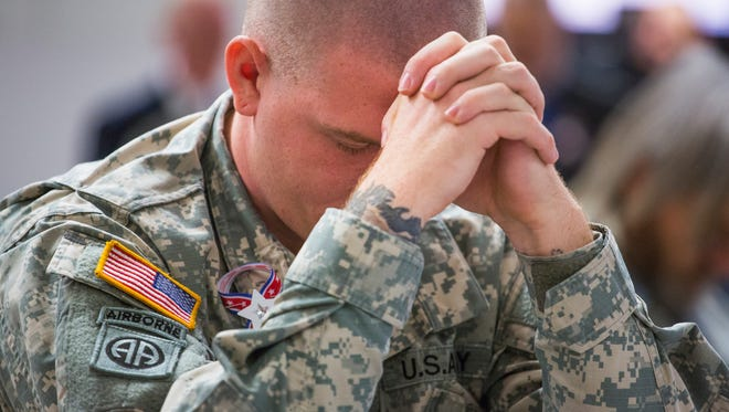 Tyler Simmons, an Army Specialist stationed at Fort Bragg, bows his head during a moment of group prayer before the start of Stuarts Draft's Veterans Day assembly on Tuesday, Nov. 10, 2015.