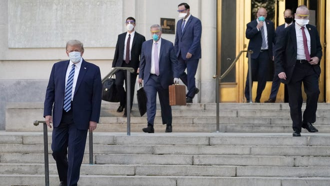 President Donald Trump, left, walks out of Walter Reed National Military Medical Center to return to the White House after receiving treatments for covid-19 on Monday in Bethesda, Md.