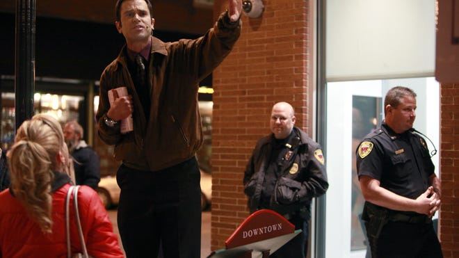 Susan Hilgert confronts downtown street preacher Aaron Brummitt, who's standing atop a battery-powered amplifier, as police keep an eye on the situation on the corner of South Avenue and Walnut Street on Friday, April 12, 2013.