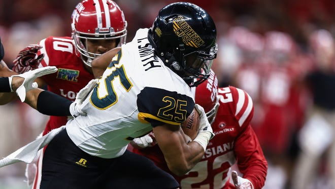 Southern Mississippi running back Ito Smith is tackled by Louisiana-Lafayette defensive back Reginald Miles during the second quarter of the R&L Carriers New Orleans Bowl.