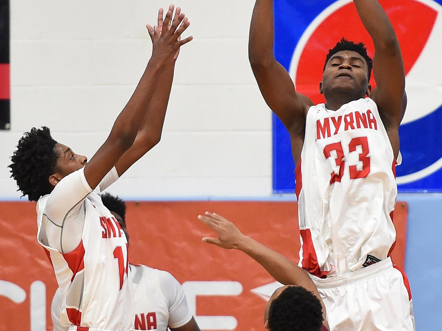Smyrna's #33 Azubuike Nwankwo grabs a rebound as The Annual Slam Dunk to the Beach Basketball Tournament started at Cape Henlopen High School in Lewes on Tuesday December 27th with Smyrna HS (white) hosting Bishop McNamara HS from Forestville, Md.