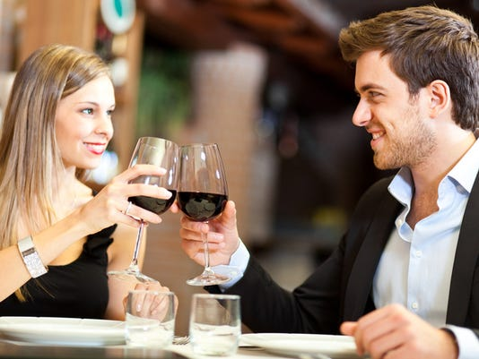 Couple in a fancy restaurant toasting wine glasses