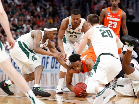 Syracuse Orange forward Oshae Brissett (11) dives for the ball in front of Michigan State Spartans forward Xavier Tillman (23) and guard Cassius Winston (5) in the first half in the second round of the 2018 NCAA Tournament at Little Caesars Arena in Detroit on March 18, 2018.