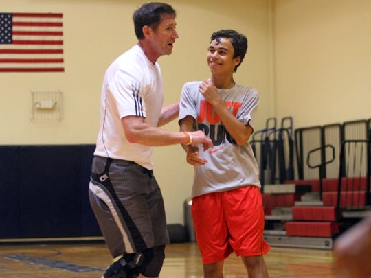 Lacey-based coach Todd Serad (left) works with a volleyball player.