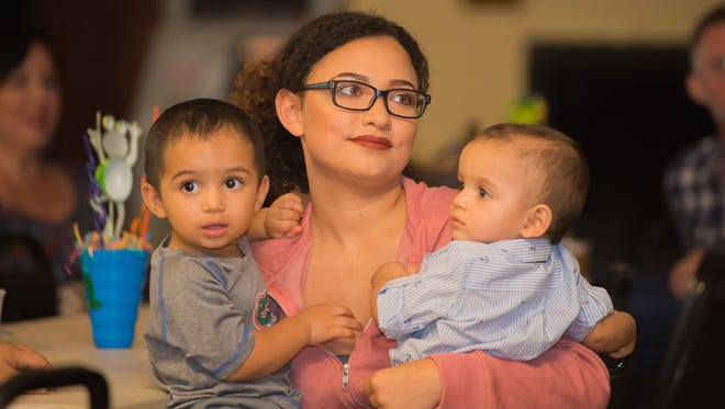 Cousin Danna Paola Lasso Nino holds Juan Pedro and Guillermo Timoteo Nino-Brown Sunday at American Legion Hall during the boys' birthday celebration and fundraiser.