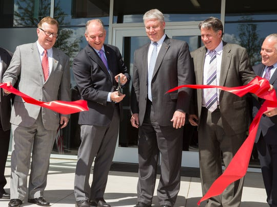 Gov. John Bel Edwards cuts the ribbon as, left to right, UL President Dr. Joseph Savoie, CGI Federal President Tim Hurlebaus and Mayor-President Joel Robideaux look on during the opening ceremony for the CGI Onshore IT Delivery Center in Lafayette.
