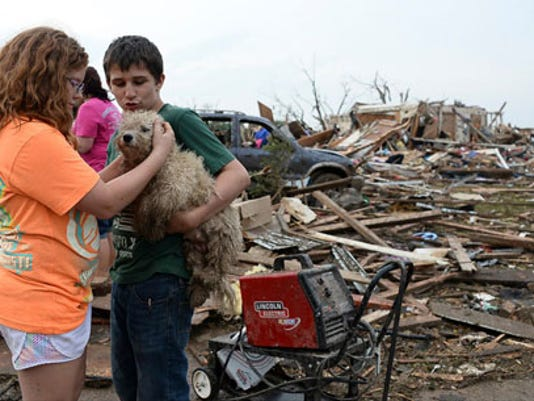 Abby Madi (L) and Peterson Zatterlee comforts Zaterlee's dog Rippy, after a tornado struck Moore, Oklahoma, May 20, 2013. A 2-mile-wide (3-km-wide) tornado tore through the Oklahoma City suburb of Moore on Monday, killing at least 51 people while destroying entire tracts of homes, piling cars atop one another, and trapping two dozen school children beneath rubble. (REUTERS/Gene Blevins)