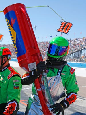Boone Stutz carries the gas can for Danica Patrick's car during the Sprint Cup race at Phoenix International Raceway.