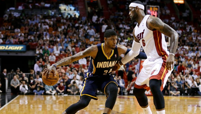 Indiana Pacers' Paul George (24) drives to the basket as Miami Heat's LeBron James (6) defends during the first half of an NBA basketball game, Friday, April 11, 2014, in Miami. (AP Photo/Lynne Sladky)
