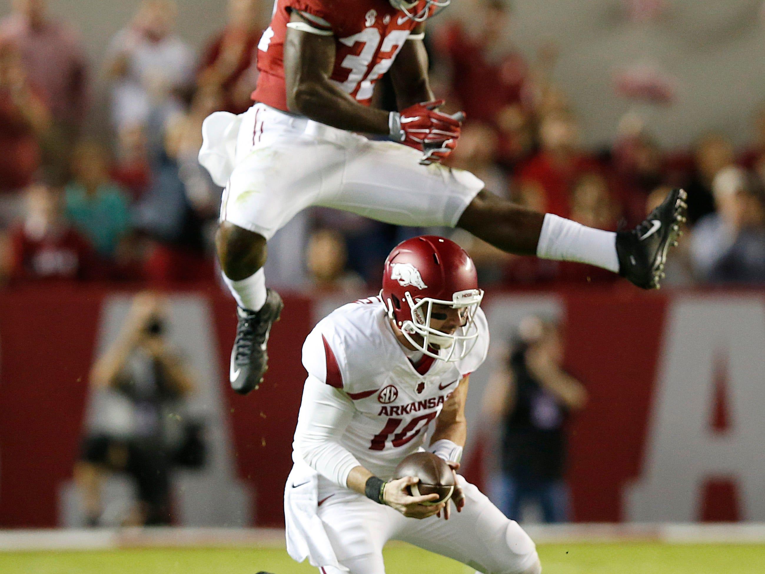 Alabama linebacker Rashaan Evans (32) jumps over Arkansas quarterback Brandon Allen (10) in the first half of an NCAA college football game, Saturday, Oct. 10, 2015, in Tuscaloosa, Ala. (AP Photo/Brynn Anderson)