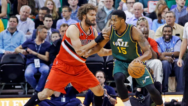 Portland Trail Blazers center Robin Lopez, left, guards Utah Jazz forward Derrick Favors (15) during the first quarter in an NBA basketball game Wednesday, March 25, 2015, in Salt Lake City.