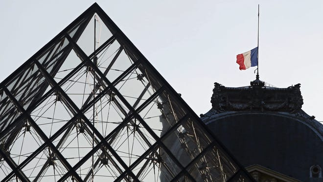A French flag hangs at half staff above the Louvre museum in Paris Nov. 15, 2015.