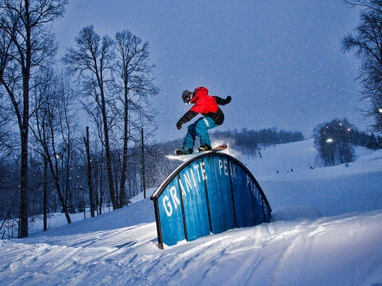 A snowboarder tackles a terrain park element at Granite