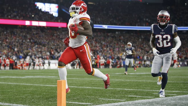Kansas City Chiefs wide receiver Tyreek Hill scores a touchdown after catching a pass in front of Patriots defensive back Devin McCourty during the game on Oct. 14, 2018, at Gillette Stadium.