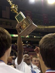 Rahlin Watson holds up the Division I state championship trophy.