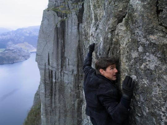 Tom Cruise hangs on a cliff edge in 'Mission: Impossible