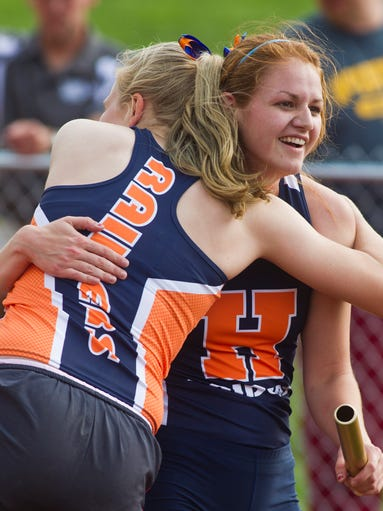 Harrison's Erin Dark is congratulated by teammate Noelle Schumacker Tuesday, May 20, 2014, after her relay took first in the 4X800 meter relay at the Harrison Girls Track Sectional at Harrison High School near West Lafayette.