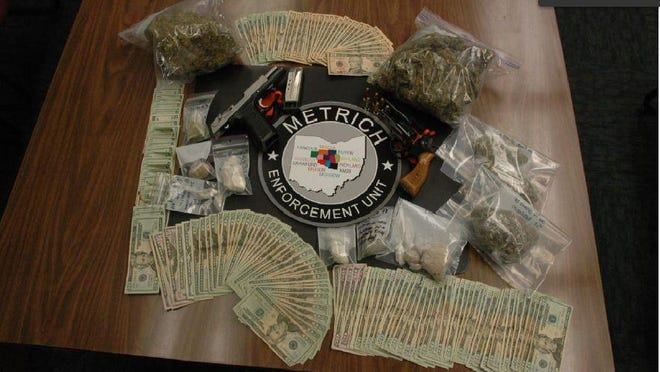 Firearms, cash, drugs and two arrested resulted from an early Thursday morning raid by METRICH and other law enforcement agencies.