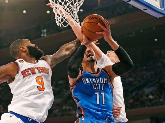 New York Knicks' center Kyle O'Quinn (9) and Knicks' forward Kristaps Porzingis (6) defend Oklahoma City Thunder center Enes Kanter (11) in the first half of an NBA basketball game in New York, Monday, Nov. 28, 2016. (AP Photo/Kathy Willens)