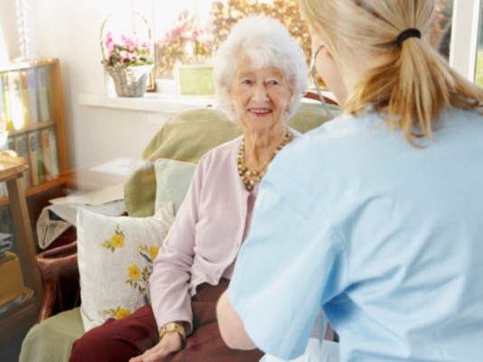 young nurse listening to senior woman's breathing in care home