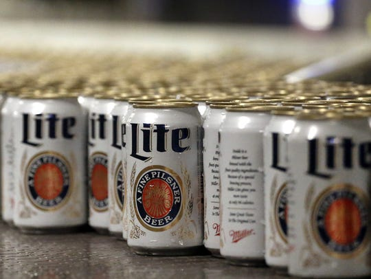 File: Newly-filled and sealed cans of Miller Lite beer move along on a conveyor belt, at the Miller-Coors Brewery, in Golden, Colo.