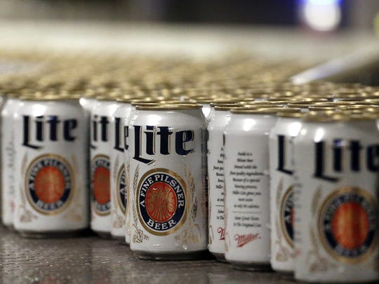 In this March 11, 2015 photo, newly-filled and sealed cans of Miller Lite beer move along on a conveyor belt, at the MillerCoors Brewery, in Golden, Colo.