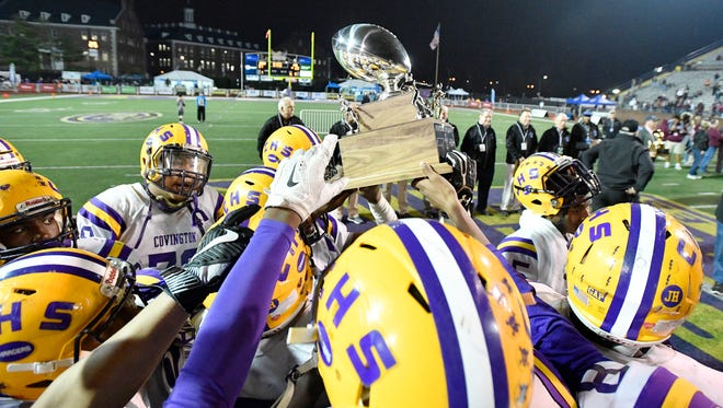 Covington players hoist their runnerup trophy after losing in the Class 3A state championship game at Tucker Stadium in Cookeville, Tenn., Thursday, Nov. 30, 2017.