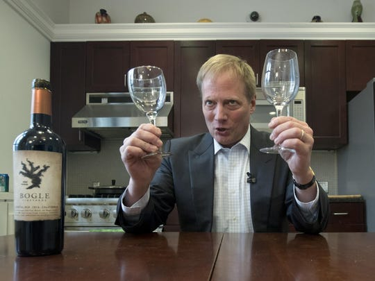 Brian Wansink, then a food behavior scientist at Cornell, holds wine glasses during a demonstration in a food lab at the university.