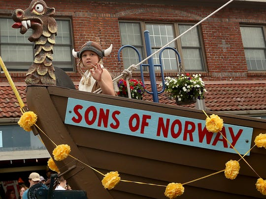 A young Viking waves to the crowd from the bow of the Sons of Norway float during the Viking Fest Parade in downtown Poulsbo, Washington on Saturday, May 19, 2018.