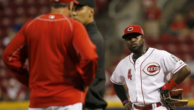 Cincinnati Reds second baseman Brandon Phillips (4) waits as Cincinnati Reds manager Bryan Price (38) talks to umpire Gabe Morales (47) after a ball off the bat of Kansas City Royals left fielder Ben Zobrist (18) (not pictured) was ruled fair in the first inning during the MLB game between the Cincinnati Reds and Kansas City Royals, Wednesday, Aug. 19, 2015, at Great American Ball Park Cincinnati, Ohio.