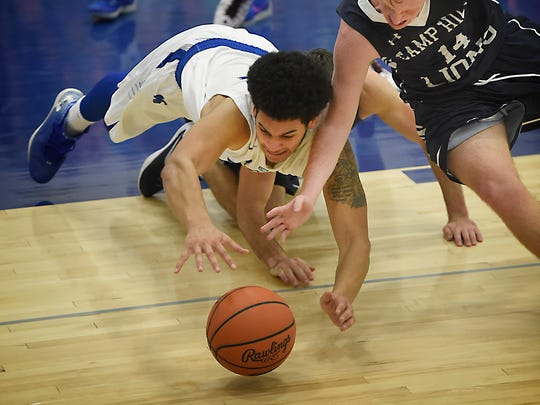 Falcons senior Raymie Ferreira and Camp Hill's Mark Leach (14) dive for a loose ball during a Cedar Crest possession Tuesday. Cedar Crest defeated Camp Hill 58-46 to win its holiday tournament title.