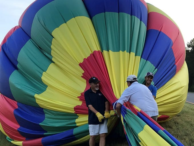 American Escapes crew pushes air out of a hot air balloon.
