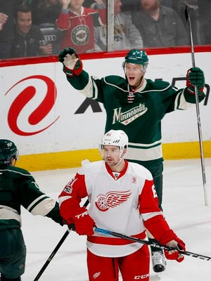 Wings defenseman Xavier Ouellet, front, watches Minnesota's Christian Folin celebrate after scoring a goal in the third period against the Red Wings on Sunday at the Xcel Energy Center in St. Paul, Minn.