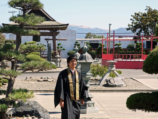 Top: Reverend Yugo Fujita stands in the garden of the