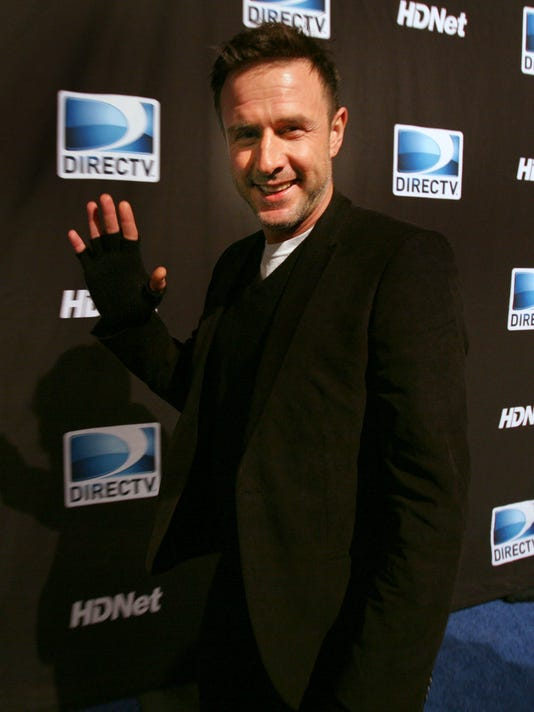 David Arquette waves on the blue carpet for the DirecTV Celebrity Beach Bowl party.