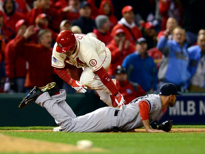 Oct. 26, 2013 -- World Series, Game 3: St. Louis Cardinals' Allen Craig is tripped by Boston Red Sox third baseman Will Middlebrooks in the ninth inning and would score on an obstruction call to win the game.