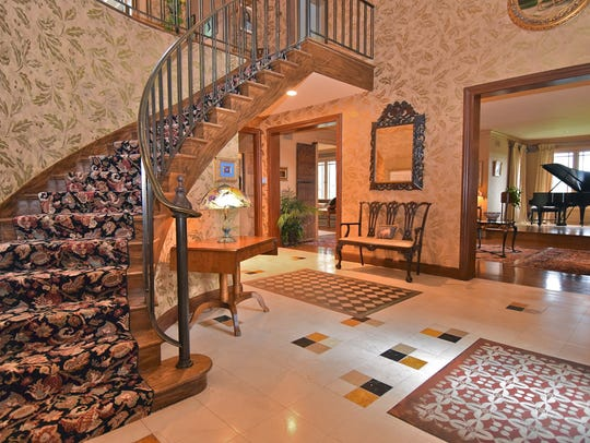 The two-story entrance foyer features a curved staircase