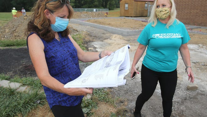 Betsy Libby (left), designer with Greencore Designs Inc., looks over plans for the new addition to the Stark County Humane Society on Tuesday, July 21, 2020. Also visible is Jackie Godbey, executive director Stark County Humane Society.