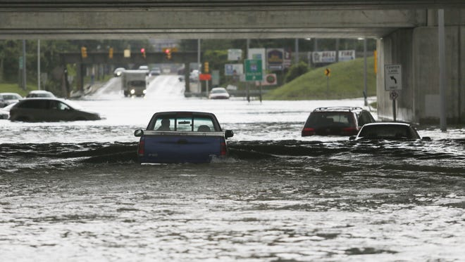 A daring driver chances flood waters that consume Oakwood Blvd. at I-94 in Melvindale stranding over 11 cars on Tuesday Aug. 12, 2014.