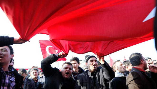 Supporters of the Fethullah Gülen movement shout slogans Dec. 14, 2014, as they wave Turkish flags   outside a courthouse in Istanbul after Turkish police began targeting Turkish media close to the movement.