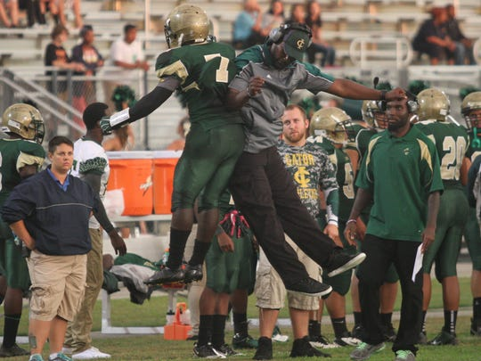 Island Coast's Van Edwards and coach Wayne Blair celebrate a touchdown against Riverdale on Friday, September 5, 2014, at Island Coast High School in Cape Coral.